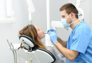 Happy dentist working making a dental hygiene to a patient